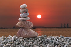 Balance stone on pile rock of sunset background in the evening. Stock Image