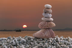 Balance stone on pile rock of sunset background in the evening. Royalty Free Stock Photography