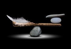 The balance of stones and feathers. The balance of the bird`s feathers and stones on dark background royalty free stock photo