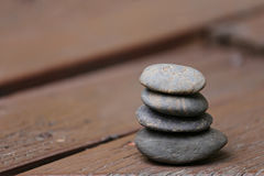 Balance Stones stacked to pyramid on brown wood background. Stock Images