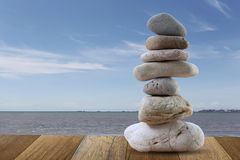 Balance Stones stacked to pyramid in sea and blue sky background Stock Photos