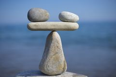 Balance of stones. To weight pros and cons. Balancing stones on the top of boulder. Close up. Royalty Free Stock Photo