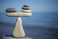 Balance of stones. To weight pros and cons. Balancing stones on the top of boulder. Close up. Stock Image