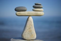 Balance of stones. To weight pros and cons. Balancing stones on the top of boulder. Close up. Balance of stones on a blue sky background with a copy space Royalty Free Stock Photos