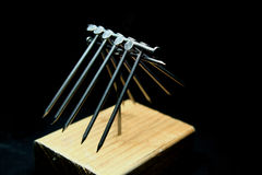 Balance success. 12 Nails balanced on top of one nail. An exercise in problem solving stock photos