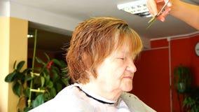 Balance tesouras profissionais ao cortar golpes a uma mulher idosa video estoque