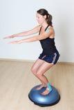 Balance training. Woman doing balance training on a balance platform Stock Photography