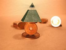 In Balance We Trust. A Pyramid balancrs on coins Royalty Free Stock Photography