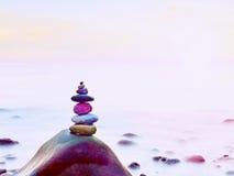 Balance von Kieseln vor dem hintergrund des unscharfen Meeres Glatte Atmosphäre auf Strand Stockfoto