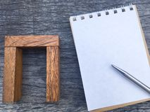 Balance wooden block beside notebook and pen for project in business team Royalty Free Stock Images