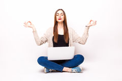 Balance in at work: Young pretty woman sitting in lotus posture on floor with laptop Stock Photography