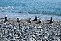 The balance of the world. sea stones have been stacked as pyramids. Sea stones have been stacked as pyramids on the beach Stock Image