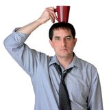 Balance Your Caffeine Intake. Businessman with tie undone, balancing his coffee mug on his head royalty free stock photography
