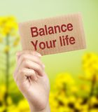 Balance your life. Brown card is holden by woman hand with beautiful natural background Royalty Free Stock Photos