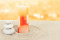 Balance zen stones and candle in sand on bokeh Royalty Free Stock Image