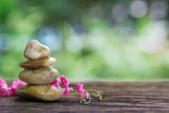 Balance Zen stones and pink flower on wood with green bokeh back royalty free stock images