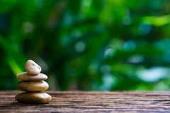 Balance Zen stones on wood with green nature bokeh background. stock images