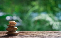 Balance Zen stones on wood with green nature bokeh background. royalty free stock photos
