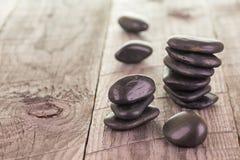 Balanced black stones on weathered deck Stock Photo