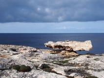 Balanced boulder on a rocky coastline scene with white stones against a calm blue sea and sky with sunlight and clouds. A balanced boulder on a rocky coastline royalty free stock image