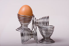 Balanced Diet. Boiled egg balanced on four metal egg cups on a white background stock image