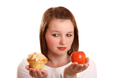 Balanced diet?. Pretty teenage girl deciding whether to choose fruit or cake to eat - and tempted by the cake Royalty Free Stock Photos