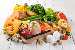 Balanced diet concept - fresh meat, fish, pasta, fruits and vegetables, nuts, seeds royalty free stock photo