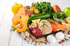 Balanced diet concept - fresh meat, fish, pasta, fruits and vegetables, nuts, seeds stock photos