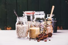 Glass jars with various legumes and grains. Balanced diet, cooking, vegetarian, raw and clean eating concept - Glass jars with various legumes and grains-beans Royalty Free Stock Image