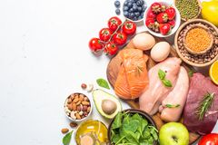 Balanced diet food background. Healthy nutrition. Ketogenic low carbs diet. Meat, fish, nuts, vegetables, oil, beans, lentils fruits and berries on white royalty free stock photos