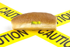 Balanced dietary warning for gluten/wheat allergy warning. (Fresh baked French roll with level tool on top of yellow caution tape Royalty Free Stock Images