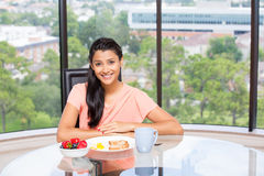 Balanced eating. Closeup portrait of a young, attractive businesswoman, kick start day with healthy breakfast, fruit bowl, egg ,green tea, smiling energetic Royalty Free Stock Photos