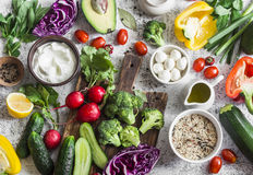 Balanced healthy diet food background in a Mediterranean style. Fresh vegetables, wild rice, fresh yogurt and goat cheese on a lig. Ht background, top view. Flat Stock Images