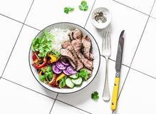Balanced lunch - grilled beef steak, vegetables and rice on a light background, top view.  royalty free stock photography