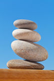 Balanced pebble stack on plain wood. Composition of the balanced pebbles Royalty Free Stock Images