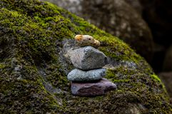 Balanced pile of stones in river. Pile of stones well balanced and placed over a mossy stone in a river stock photo