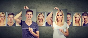 Balanced relationship concept. Masked young woman and man expressing different emotions royalty free stock image