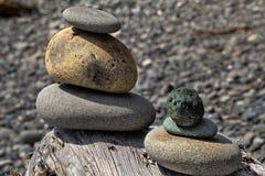 Balanced rocks on log Stock Photo
