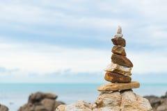Balanced stone pyramid on green water of ocean. stock image