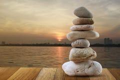 Balanced stone of pyramid for meditation. Balanced stone of pyramid for meditation on brown wood floor and coast at Sunrise Stock Photo