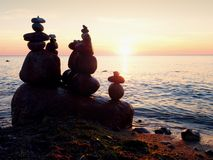 Balanced stone pyramid on sea shore, romantic sunset at horizon Royalty Free Stock Photography