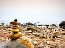Balanced stone pyramid on sea shore, waves in background. Colorful flat stones. For meditation lying on sea Stock Image