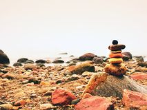 Balanced stone pyramid on sea shore, waves in background. Colorful flat stones. For meditation lying on sea Stock Photo