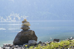 Balanced stone pyramid on shore of blue water of mountain lake Stock Photography