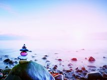 Balanced stone pyramide on shore of blue water of ocean. Blue sky in water level mirror Stock Photos