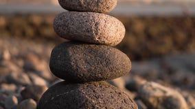 Balanced stone pyramide on shore of the ocean at dawn. Sea pebbles tower closeup symbolizing stability, zen, harmony