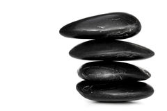 Balanced Stones. Balanced black river stones, isolated on white with soft shadow Royalty Free Stock Images