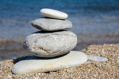 Balanced stones on the beach. Stones stacked in a pyramid on the beach in Greece royalty free stock photos