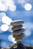 Balanced stones over blue sea. Close-up of balanced pebbles stack over blue sea Stock Photos