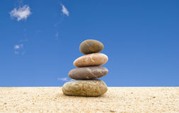The balanced stones on sand. Against the blue sky Stock Images